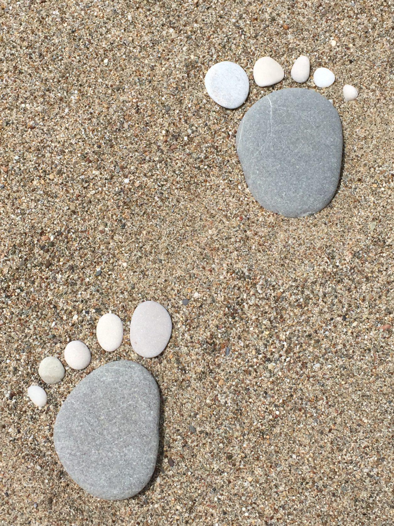 Fussabdruck aus Steinen an schnem Sandstrand